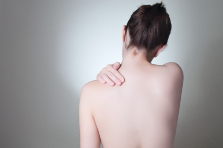 woman back of head: Rear view of a young woman touching her back