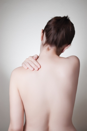 arthritis back: Rear view of a young woman touching her back