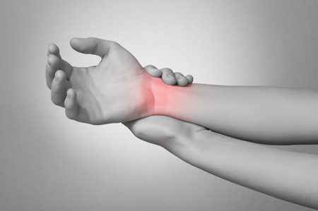 Une jeune femme de toucher son poignet douloureux Banque d'images