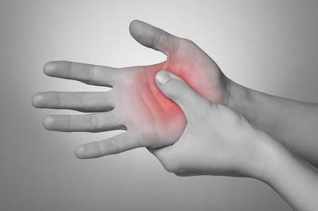 masoterapia: Una joven mujer masajear su mano dolorosa Foto de archivo