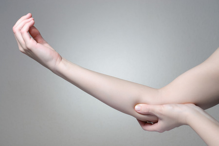 touching hands: A young woman touching her painful elbow Stock Photo
