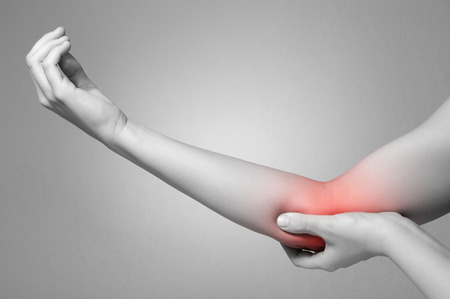 broken wrist: A young woman touching her painful elbow Stock Photo