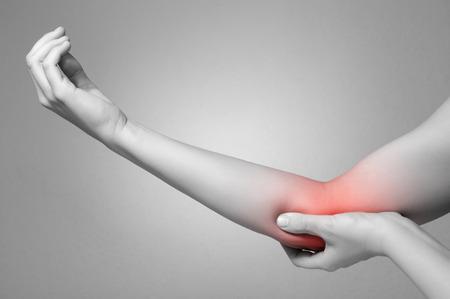 arm: Una giovane donna di toccare il gomito doloroso