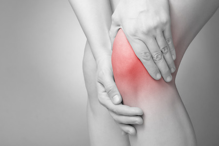 rheumatism: A young woman massaging her painful knee