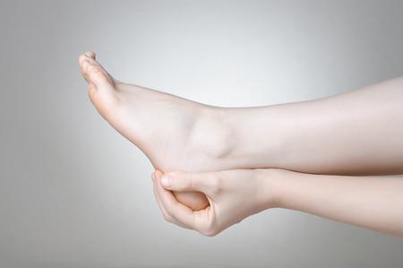 pierna rota: Una joven mujer masajear su dolorosa talón Foto de archivo