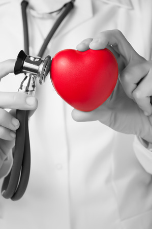 Red heart and stethoscope in a doctor s hand photo