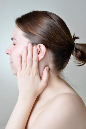 Young woman touching her painful ear Foto de archivo