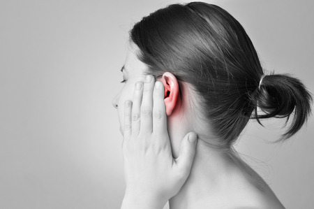 infection: Young woman touching her painful ear Stock Photo