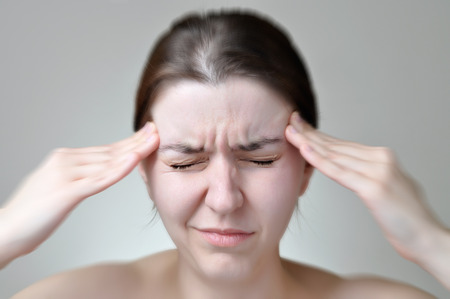 A young woman holding her painful head