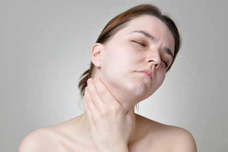 pharyngitis: Young woman holding her painful throat