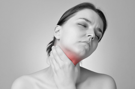 Young woman holding her painful throat photo