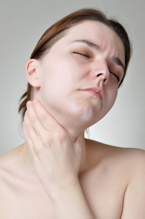 Young woman holding her painful throat