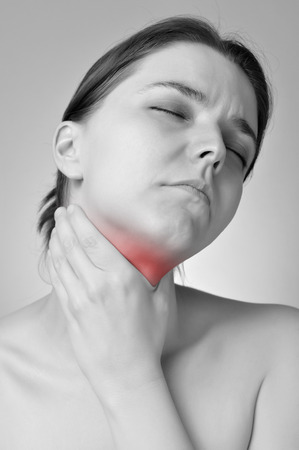 hypothyroidism: Young woman holding her painful throat