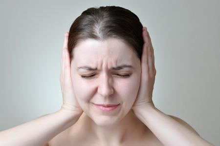 contaminacion acustica: Mujer joven que cubre sus o�dos