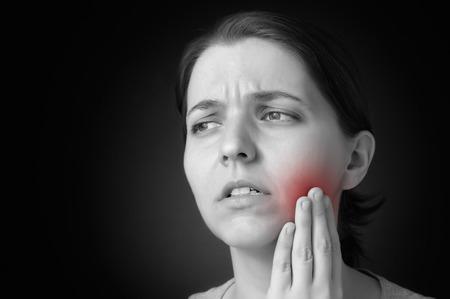 dolor de muelas: Mujer joven que tiene dolor de muelas