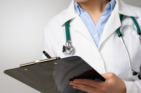 Female doctor taking notes on clipboard