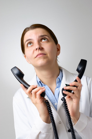 annoy: Annoyed female doctor with two phone receivers Stock Photo