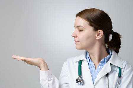 Female doctor showing copyspace on her palm photo