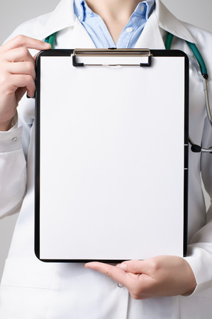 Female doctor showing a clipboard with blank paper photo