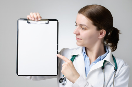 Female doctor pointing at a clipboard with blank paper photo