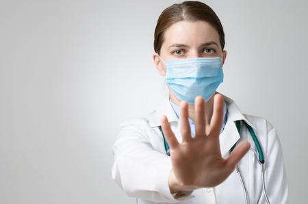 Vrouwelijke arts in gezichtsmasker met stop teken met haar hand Stockfoto