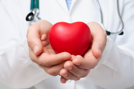 Female doctor protecting a red heart with her hands Stock Photo