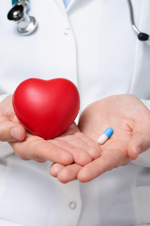 heart pain: Female doctor showing a red heart and a blue pill Stock Photo