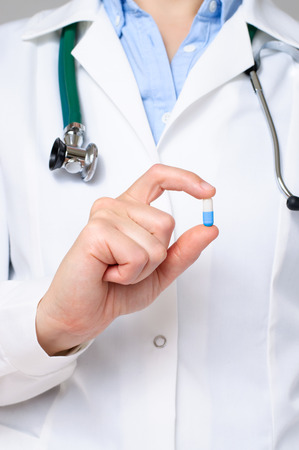 Female doctor showing a blue pill photo