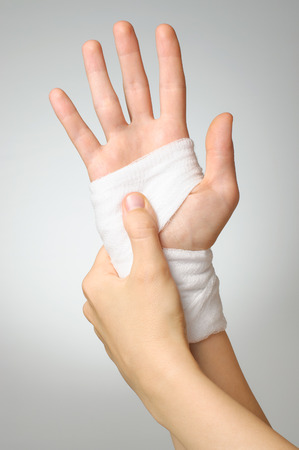 wrist pain: Injured painful hand with white bandage