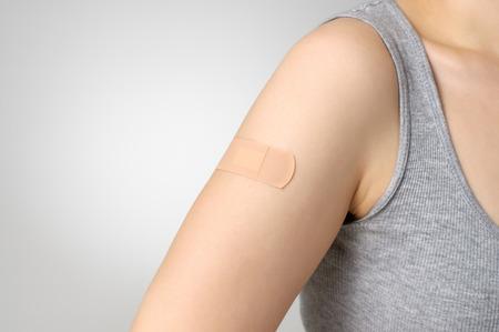 Female arm with adhesive bandage