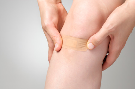 body wound: Woman putting an adhesive bandage on her leg