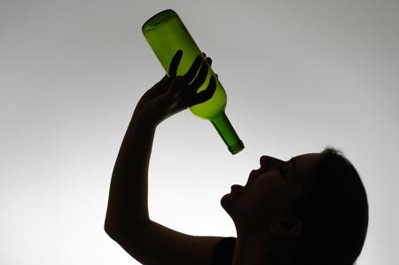 tomando alcohol: Silueta de una mujer alcoh�lica con una botella