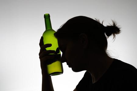 ワインの瓶と女性のシルエット
