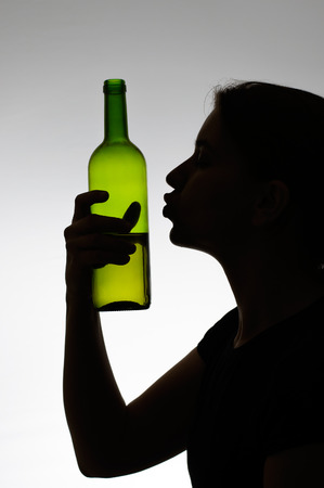 anonym: Silhouette of a woman kissing a wine bottle