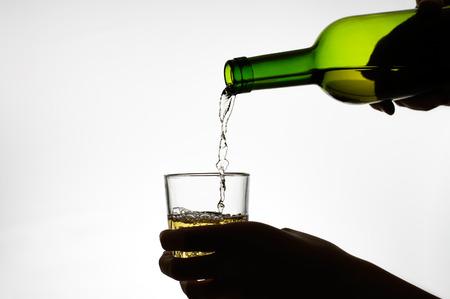 alcoholismo: Silueta de una mano vertiendo el vino de una botella Foto de archivo