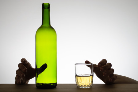 Silhouette of hands reaching for a glass of wine and a wine bottle photo