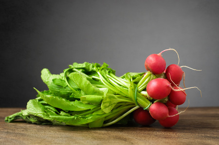 A bunch of fresh radishes on wooden table Stock Photo