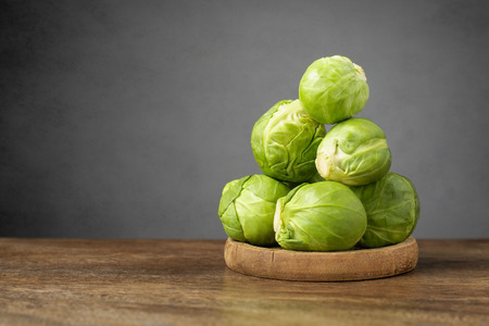 brussels sprouts: A heap of fresh brussels sprouts on wooden table Stock Photo