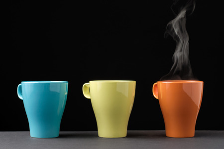 steaming cup of coffee: Three colorful mug in a row. One with steam.