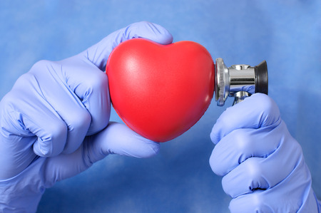 cardiosurgery: Red heart and stethoscope in the hand of a doctor
