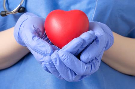 ataque al corazón: Doctor de sexo femenino que sostiene una forma de corazón rojo Foto de archivo