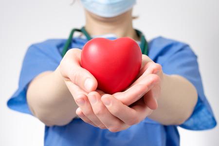 붉은 심장 모양을 잡고 여성 의사