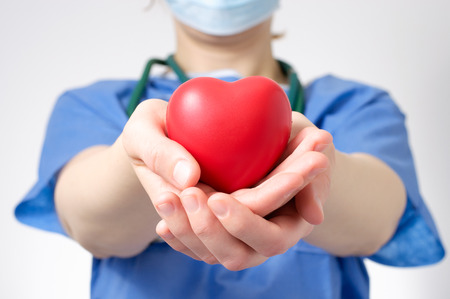 donating: Female doctor holding a red heart shape