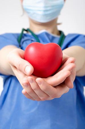 donacion de organos: Doctor de sexo femenino que sostiene una forma de corazón rojo Foto de archivo