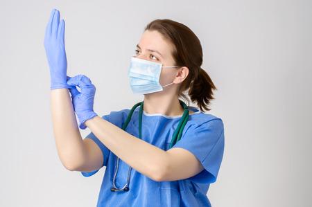 Female doctor putting on blue surgical gloves Standard-Bild