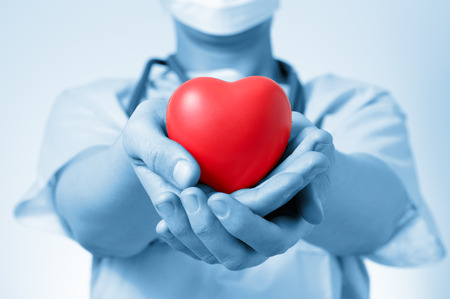 Female doctor holding a red heart shape