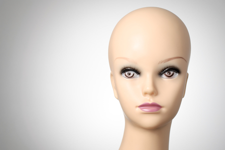 bald girl: Mannequin head on grey background with copyspace Stock Photo