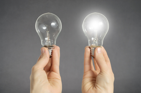 right choice: Decision making concept. Hands holding two light bulbs, one of them is glowing Stock Photo