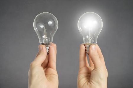 toma de decision: La toma de decisiones concepto. Manos que sostienen dos bombillas, una de ellas está brillando Foto de archivo