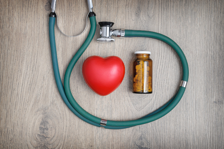 Overhead view of a stethoscope, a glass of pills and a red heart shape